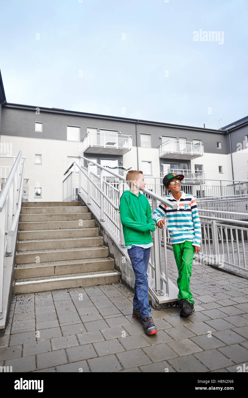 Boys (8-9) standing by stairs and talking - Stock Image