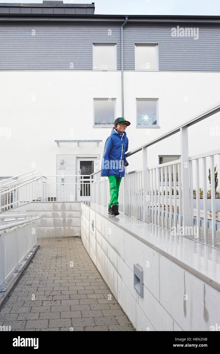 Boy (8-9) walking on top of wall by railing - Stock Image