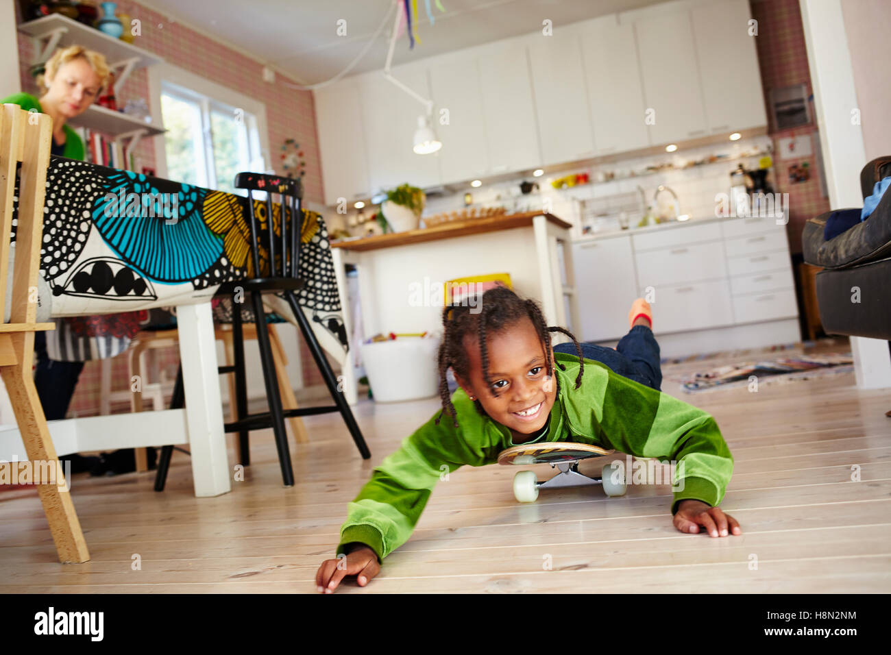 Girl (6-7) lying on skateboard on kitchen floor Stock Photo