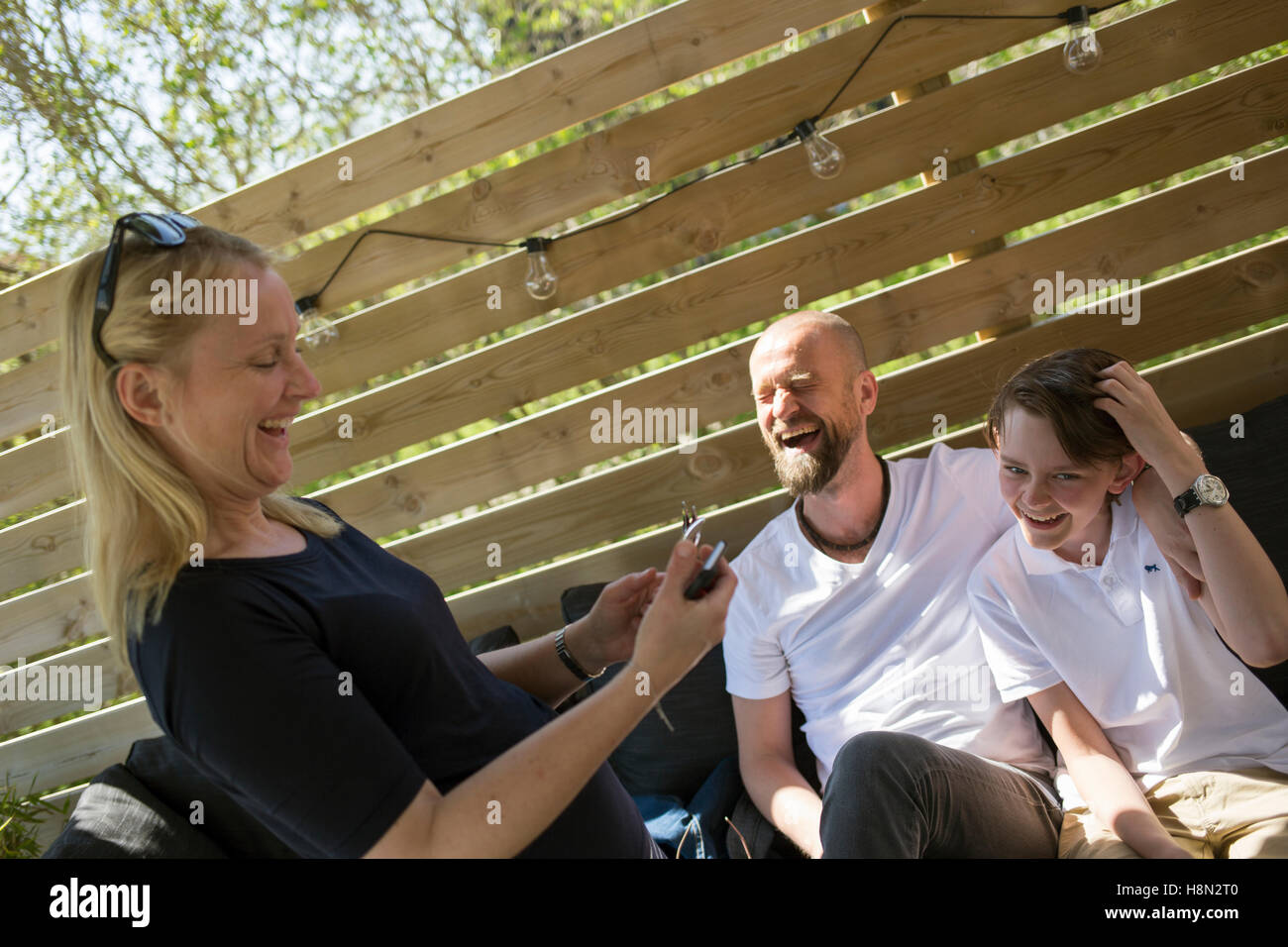 Parents with son (14-15) laughing - Stock Image