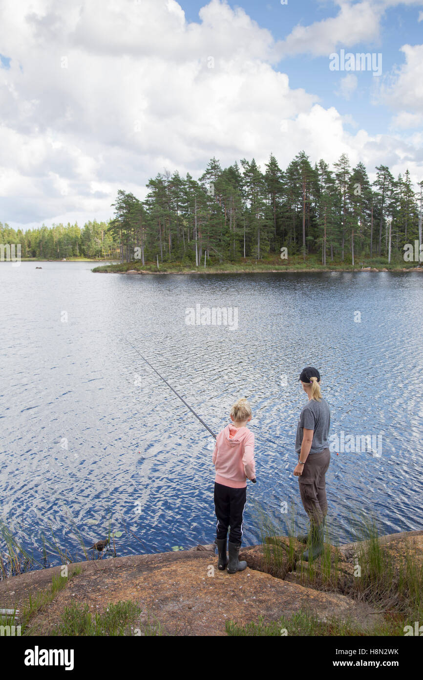 Mature woman and girl (12-13) fishing in lake - Stock Image