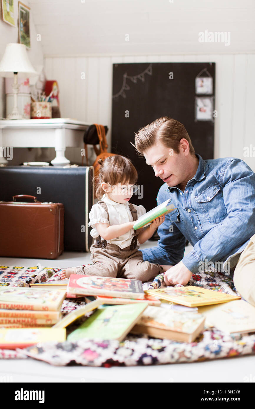 Father reading with daughter (2-3) picture book - Stock Image