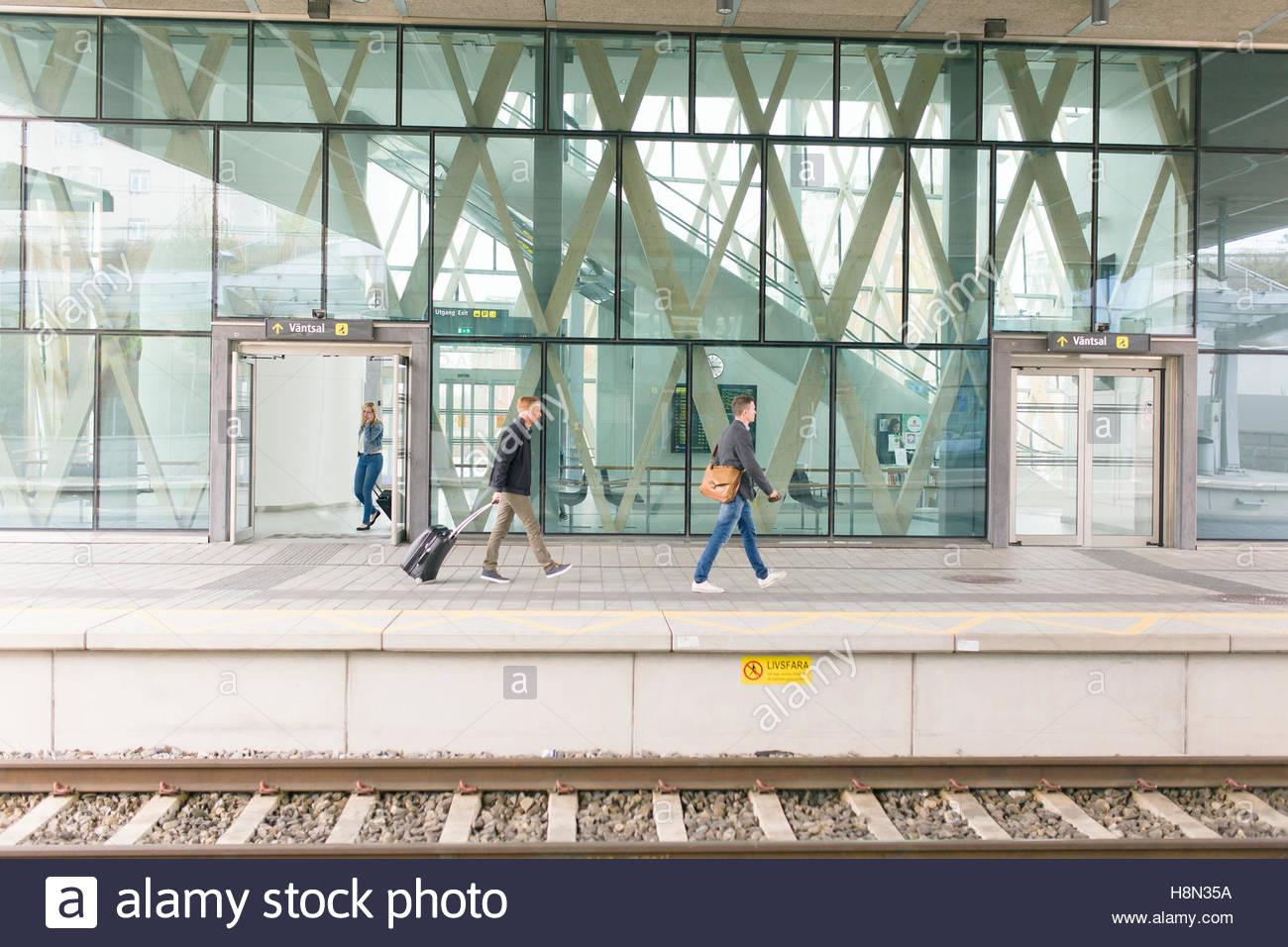 Woman and men on railroad station platform - Stock Image