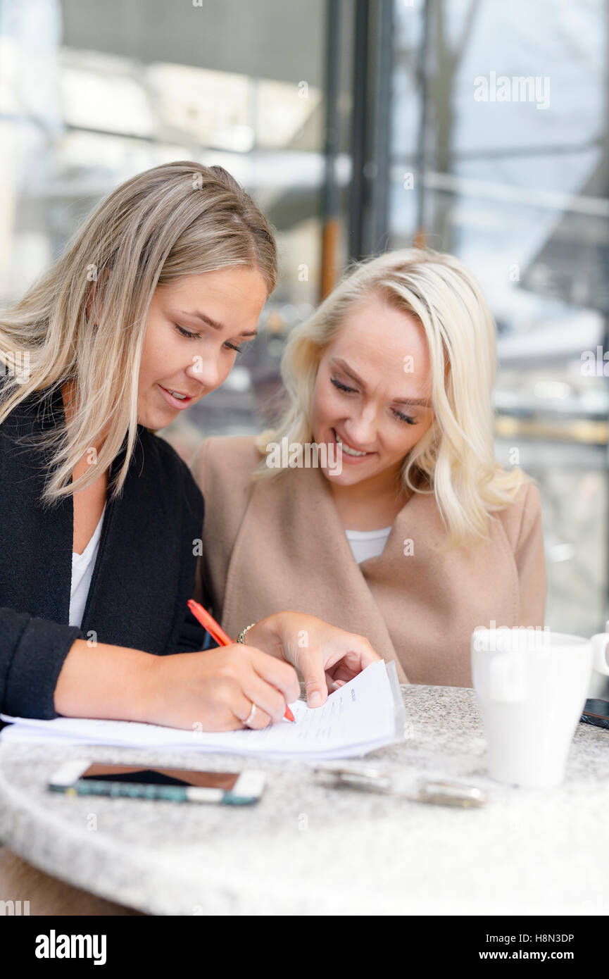 Young women filling in documents at outdoor cafe - Stock Image