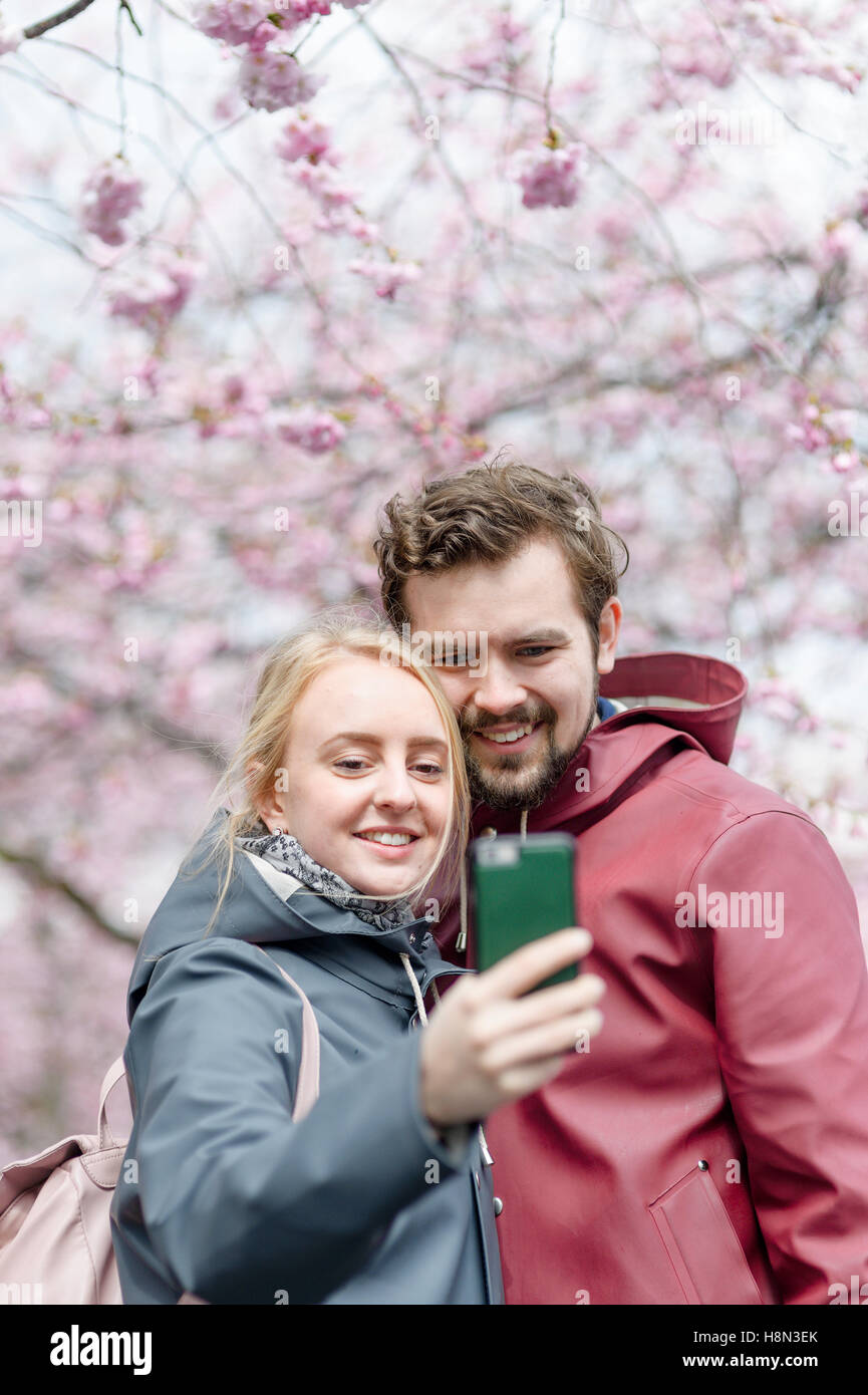 Young couple taking selfies under blooming trees - Stock Image