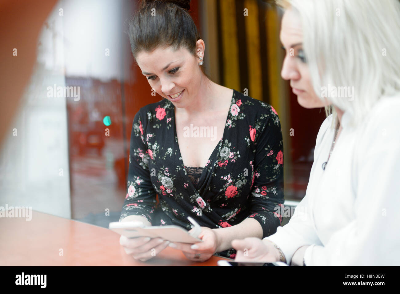 Young women using mobile phones at cafe - Stock Image