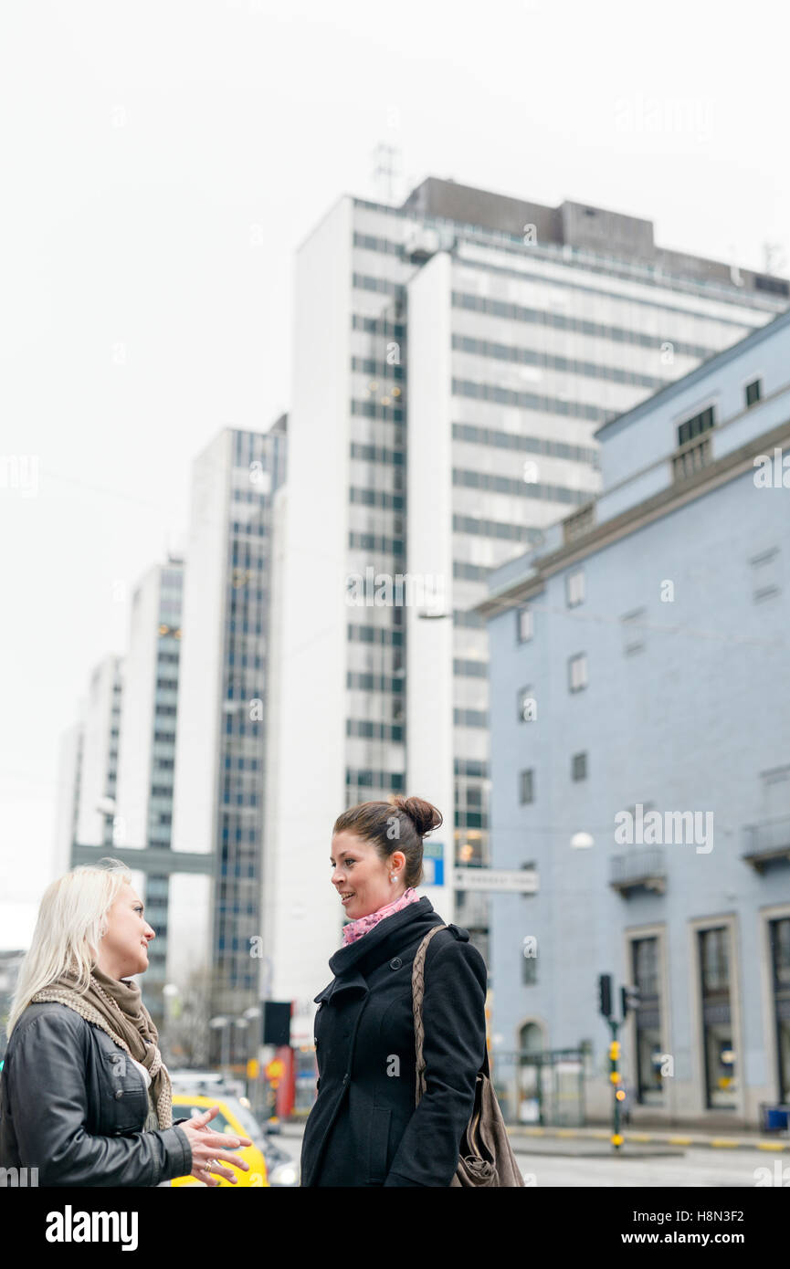 Mid adult women talking in street - Stock Image