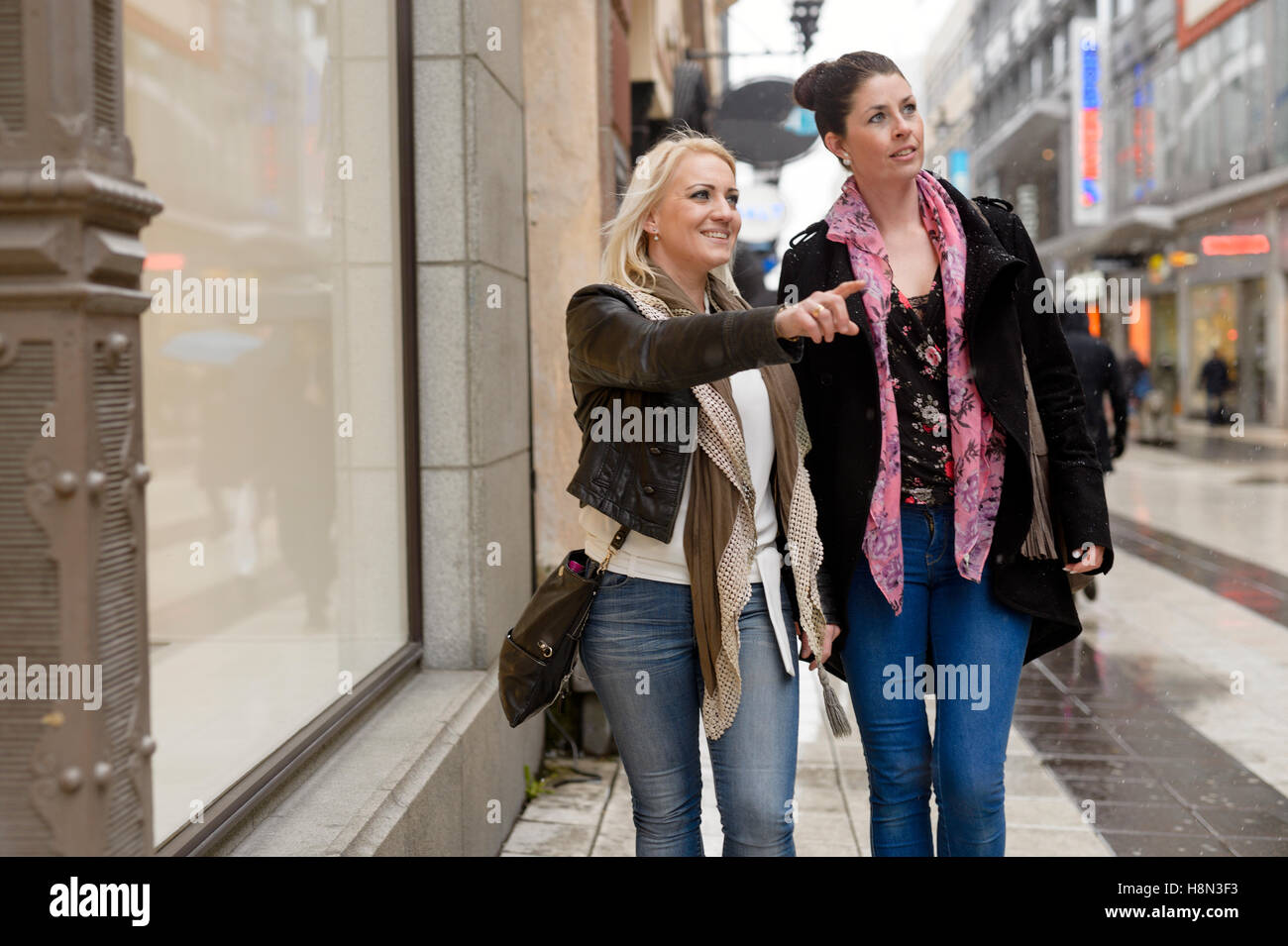 Mid adult women walking down street - Stock Image