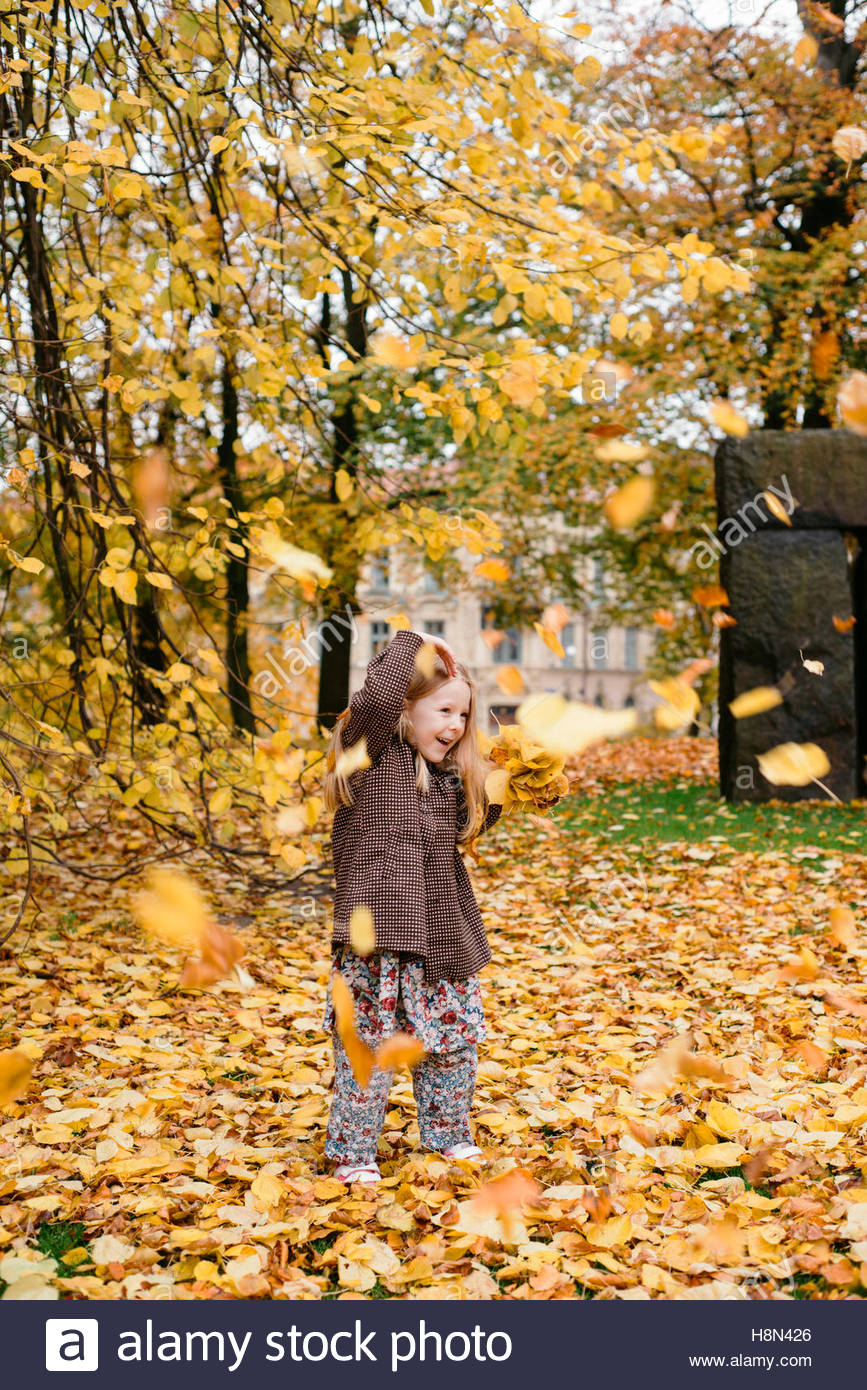 Leaves falling on girl (4-5) in park - Stock Image