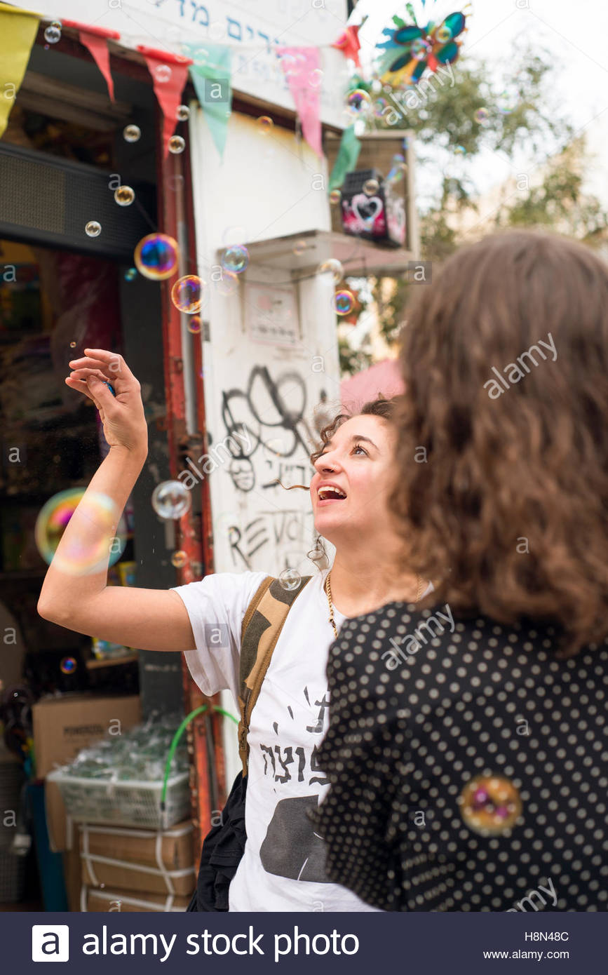 Woman looking on bubbles in street - Stock Image