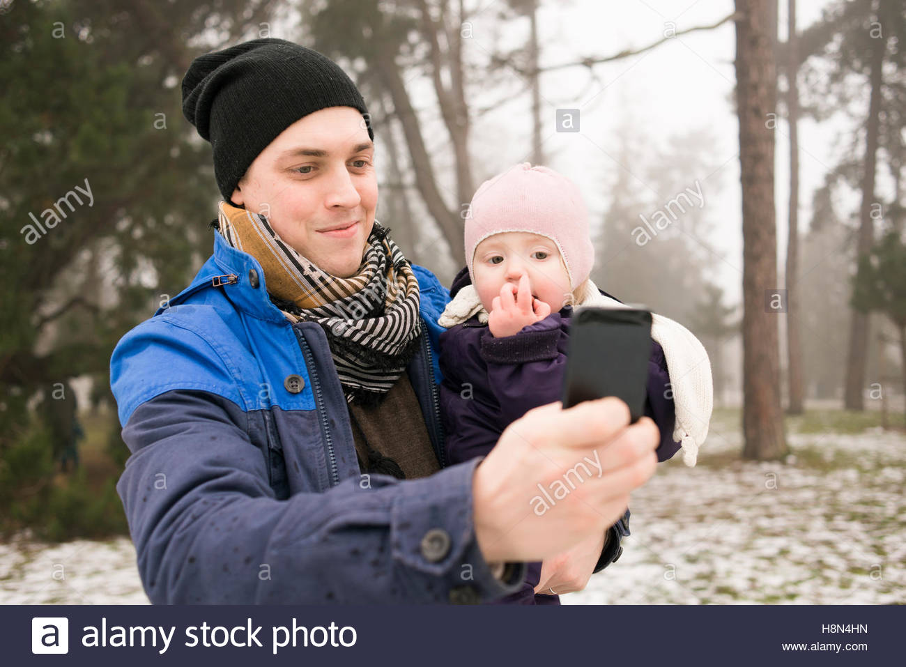 Young man taking selfie with daughter (12-17 months) in park - Stock Image