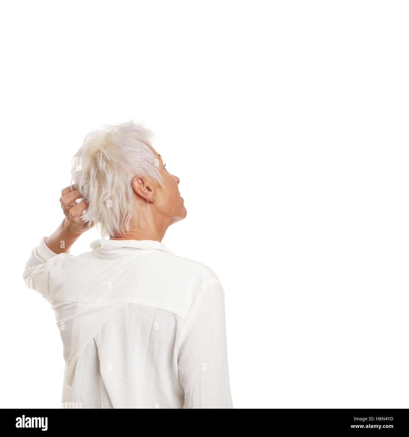 puzzled older woman scratching her head - Stock Image