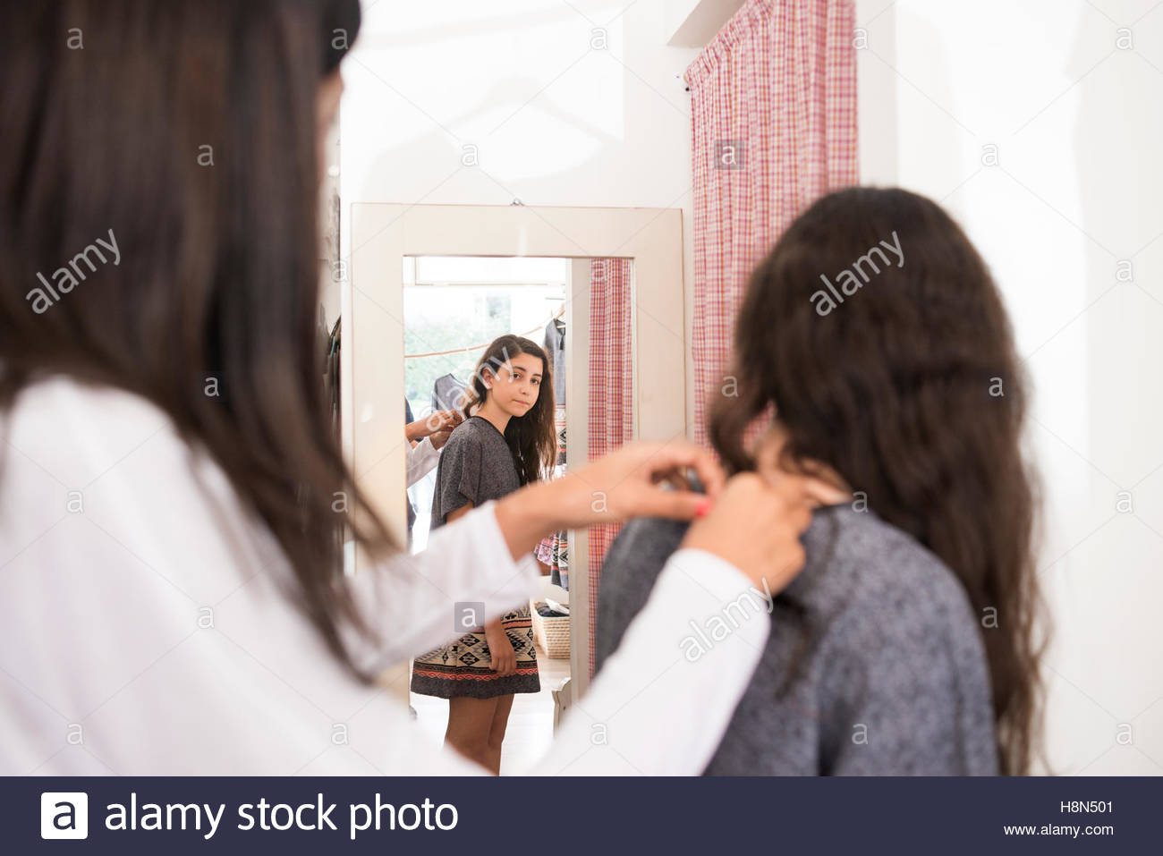 Mature woman and girl (10-11) in clothes store - Stock Image