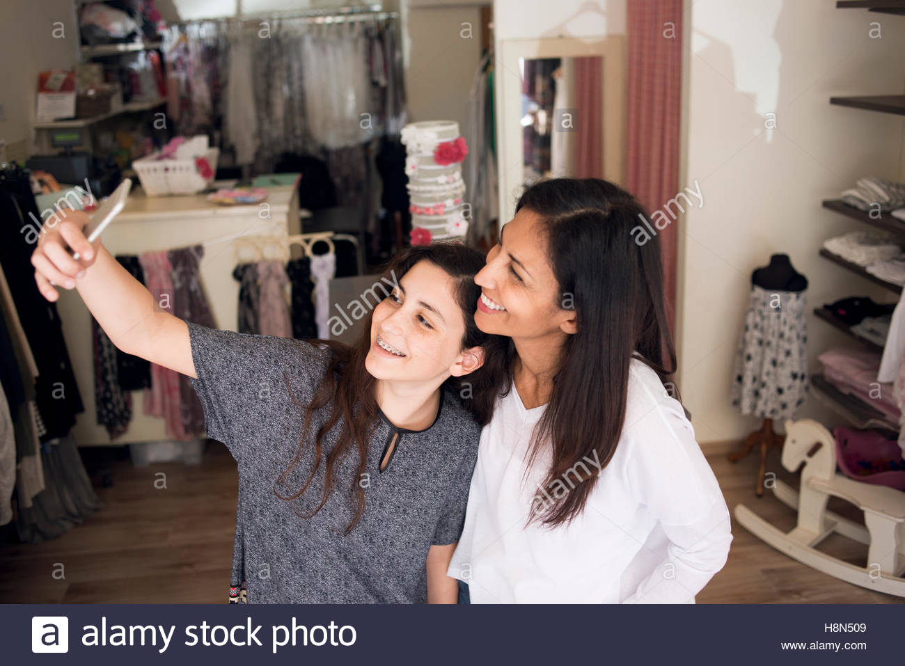 Mature woman and girl (10-11) taking selfie in clothes store - Stock Image