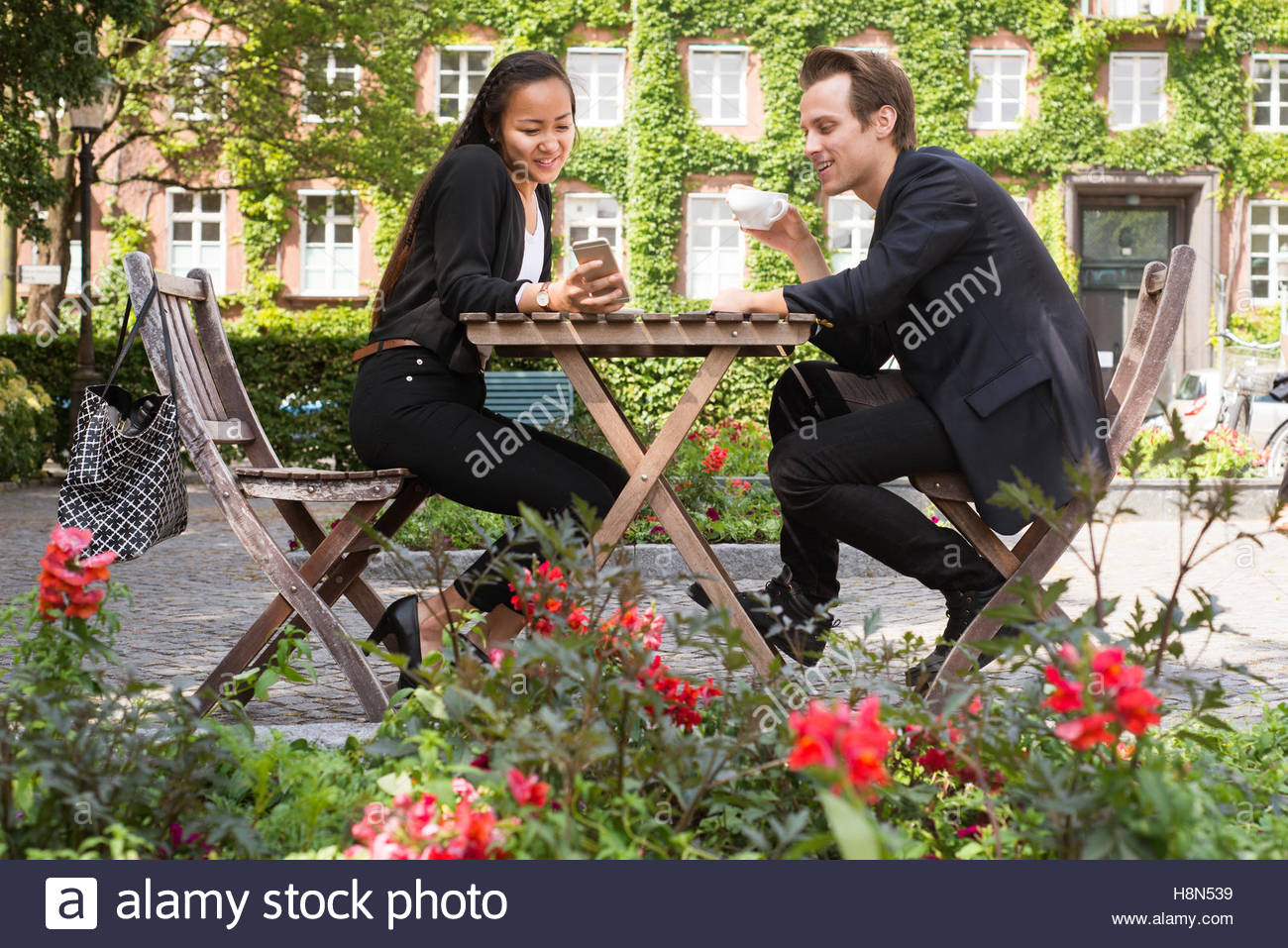 Young woman and man sitting at table and looking at smart phone - Stock Image