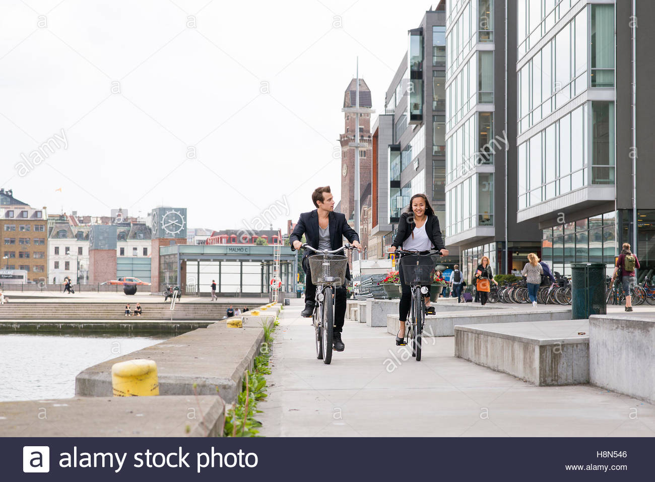 Young woman and man cycling by river - Stock Image