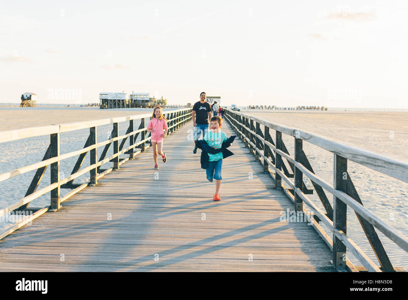 Father with daughter (10-11) and son (8-9) running along boardwalk - Stock Image