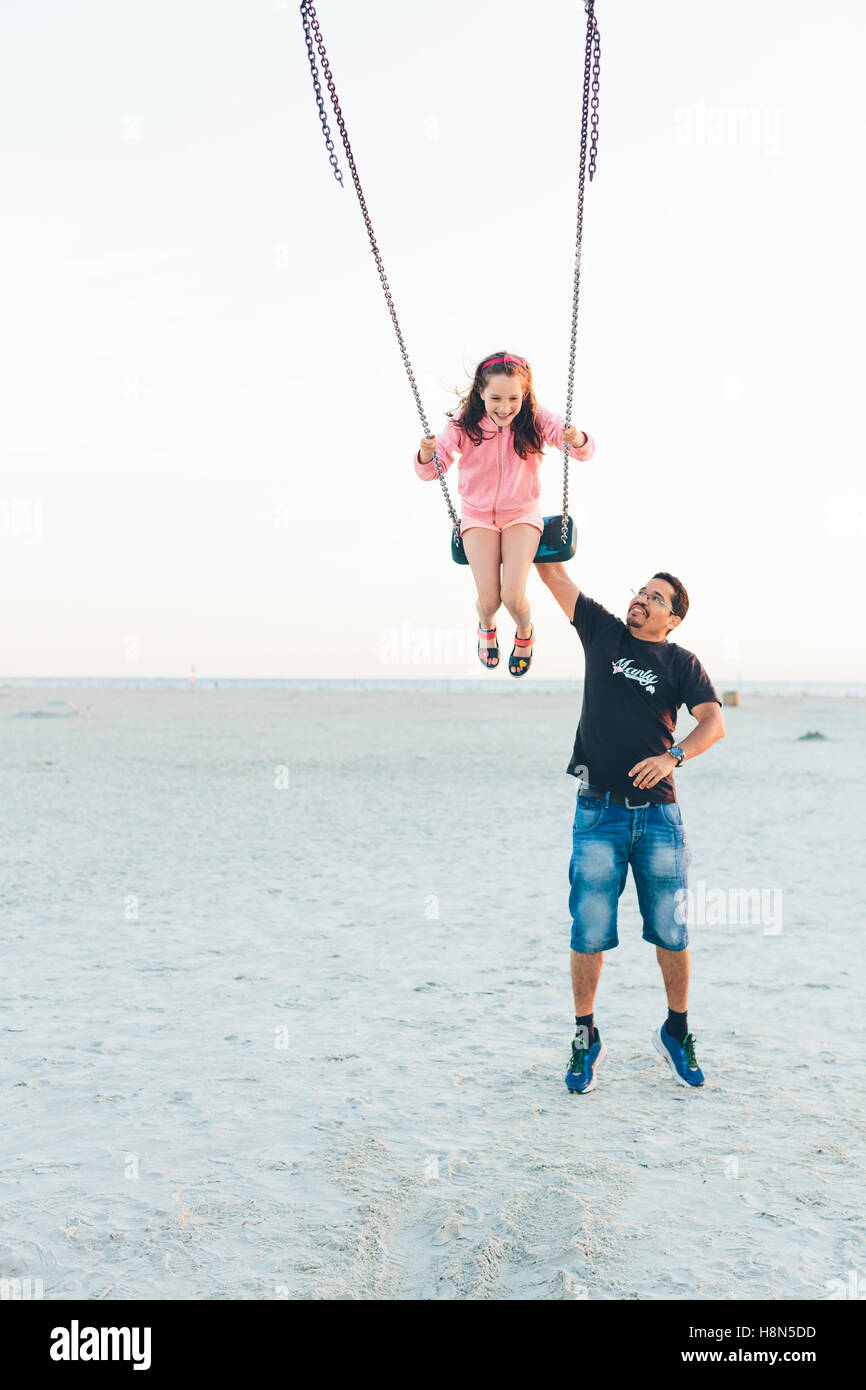 Father pushing daughter (10-11) on swing at beach - Stock Image
