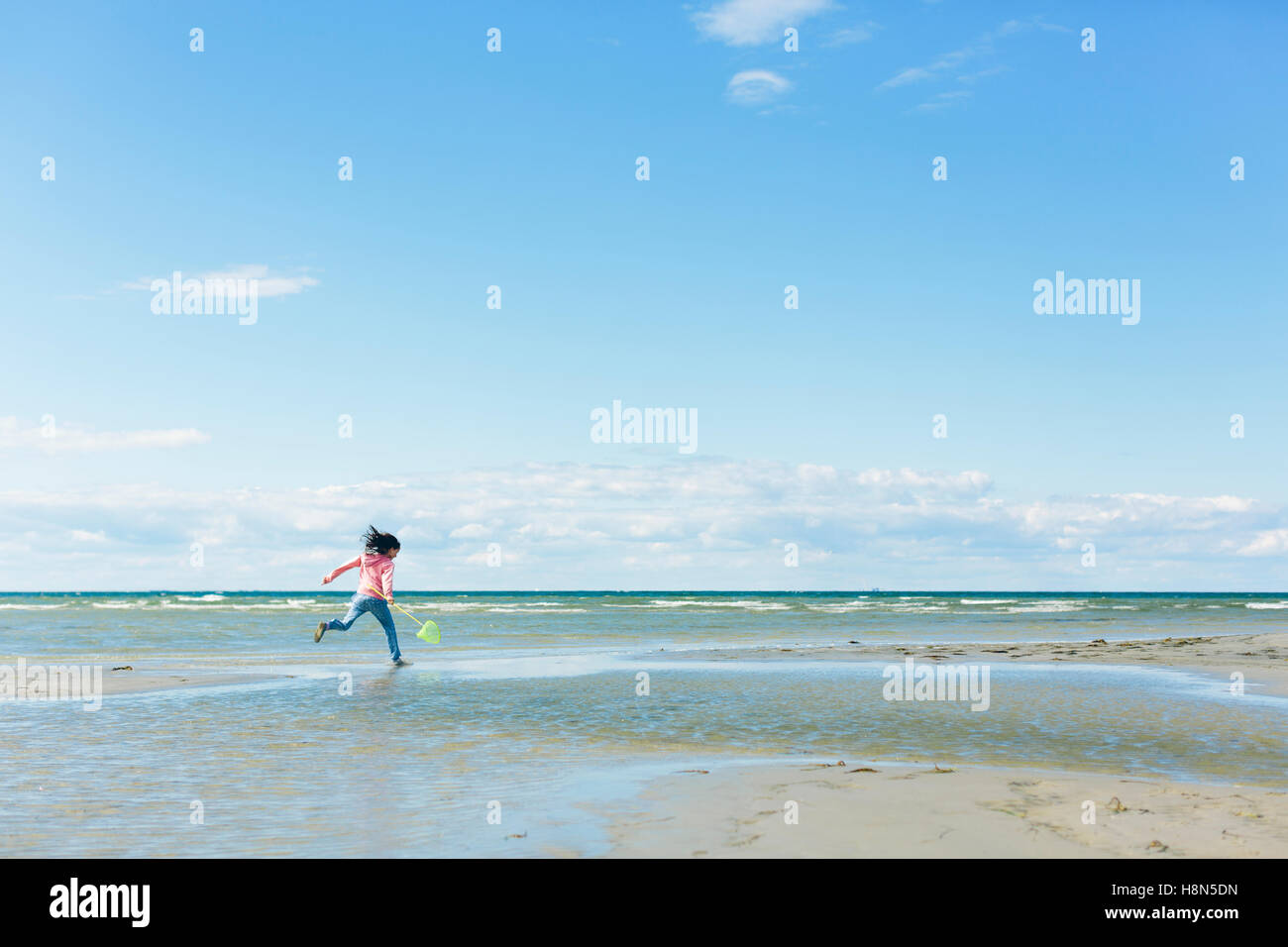 Girl (10-11) running on beach - Stock Image