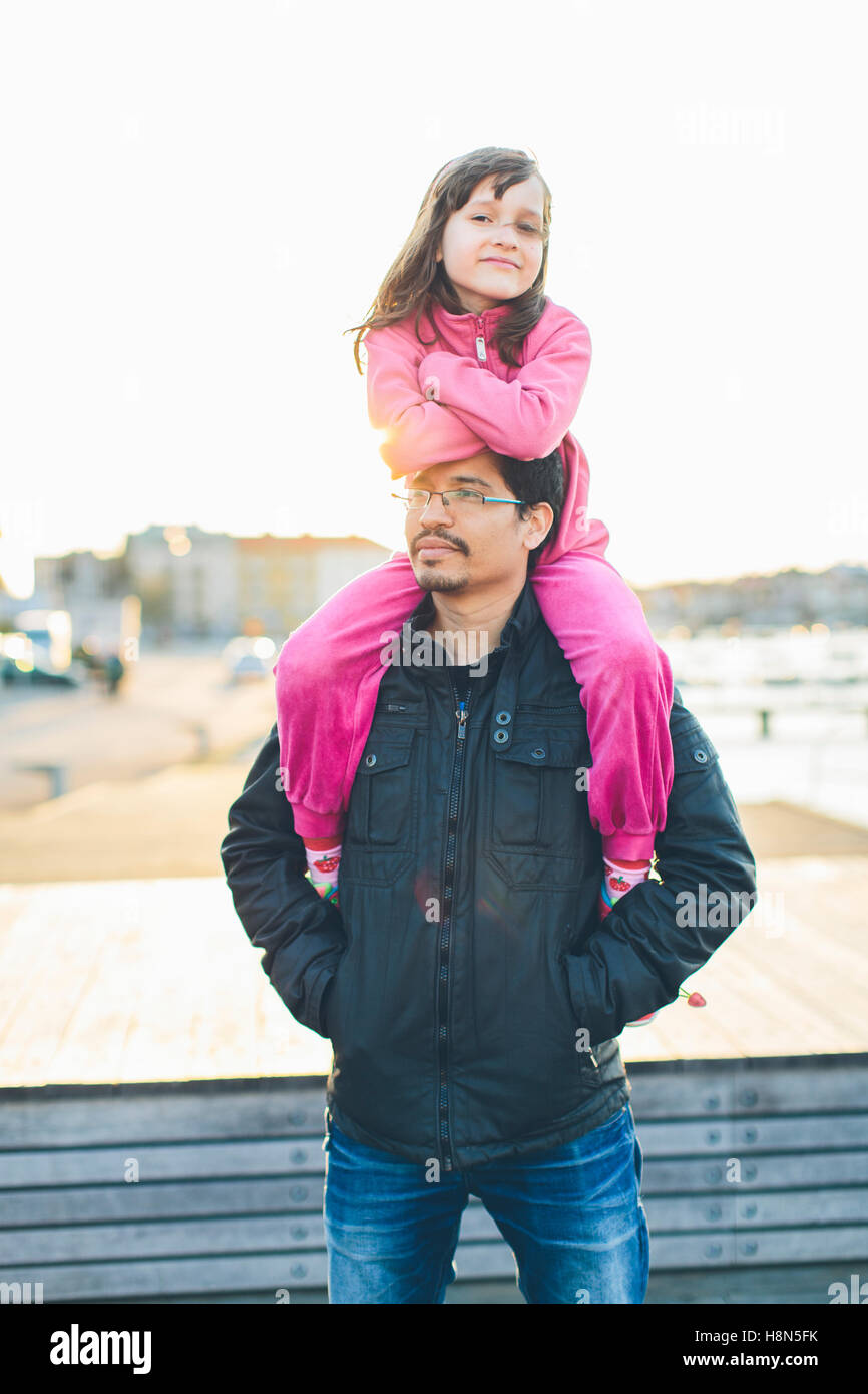 Father carrying daughter (10-11) on shoulders - Stock Image