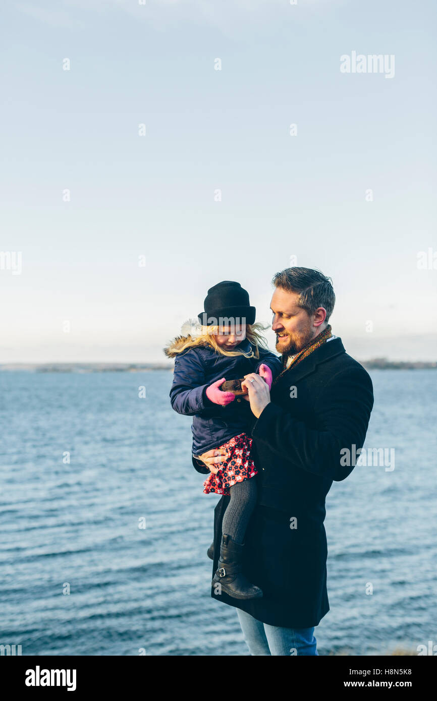 Father with daughter (4-5) standing by sea Stock Photo