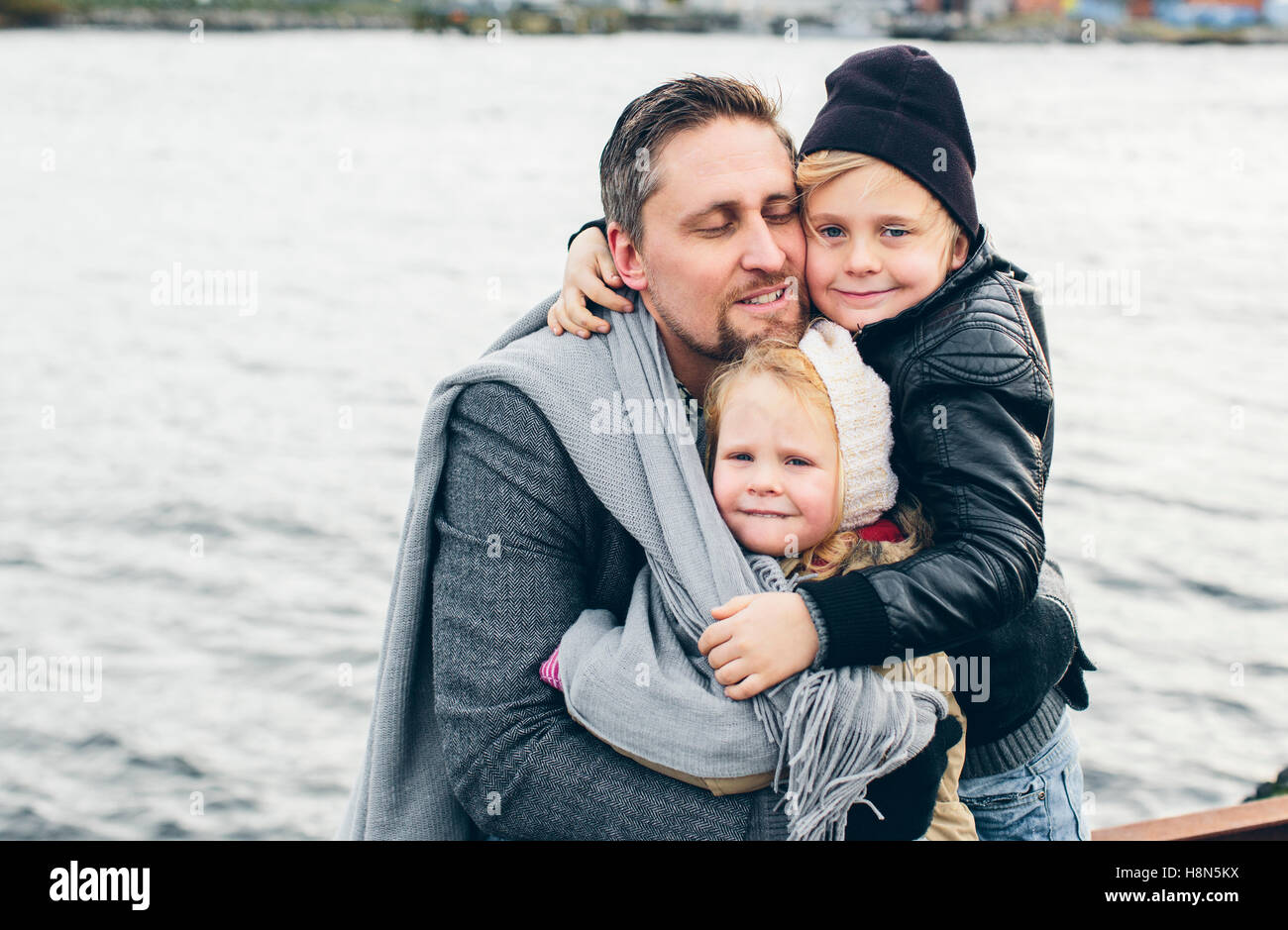Father with two children (2-3, 6-7) by lake - Stock Image