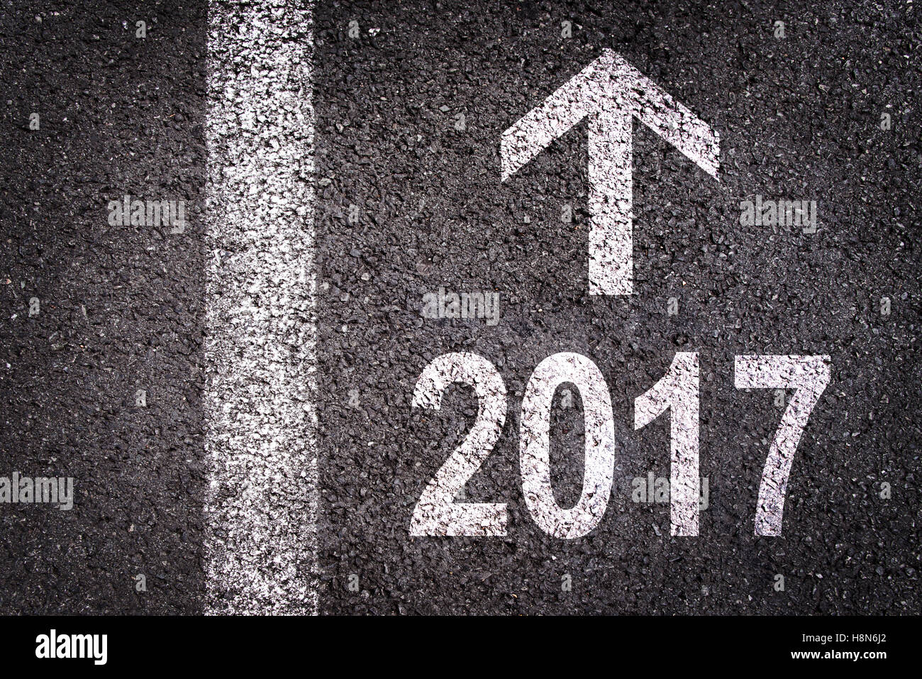 2017 and an arrow written on an asphalt road background - Stock Image