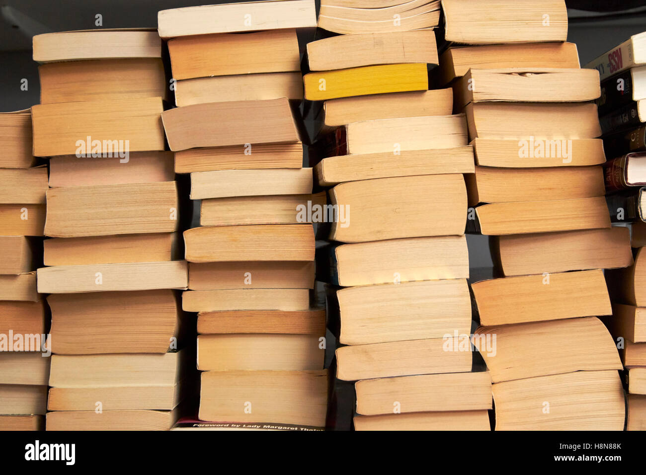 pile of stacks of used paperback books in the uk - Stock Image