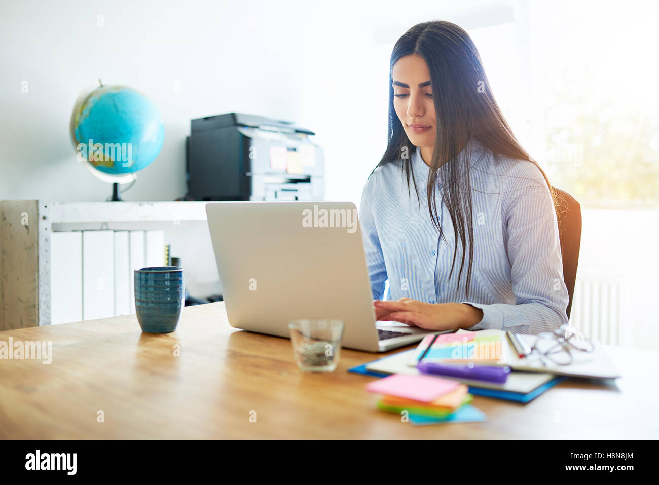 Competent young business secretary working at a laptop at a wooden desk surrounded by colorful memo notes to organise - Stock Image