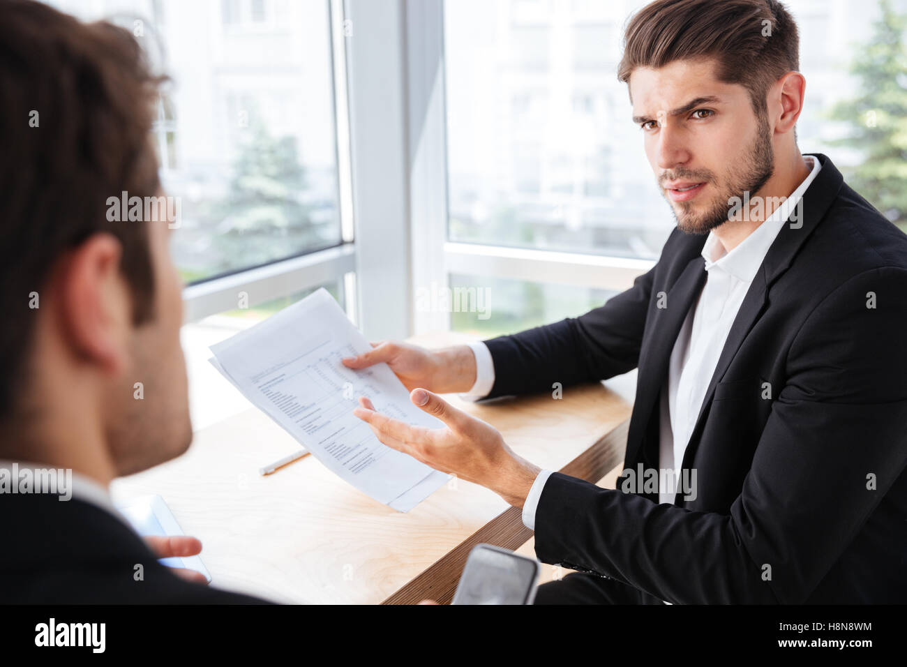 Serious young businessman sitting and giving documents to his colleague in office - Stock Image