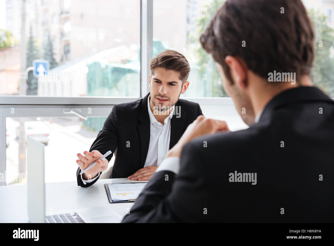 Two concentrated young businessmen working with laptop in office - Stock Image