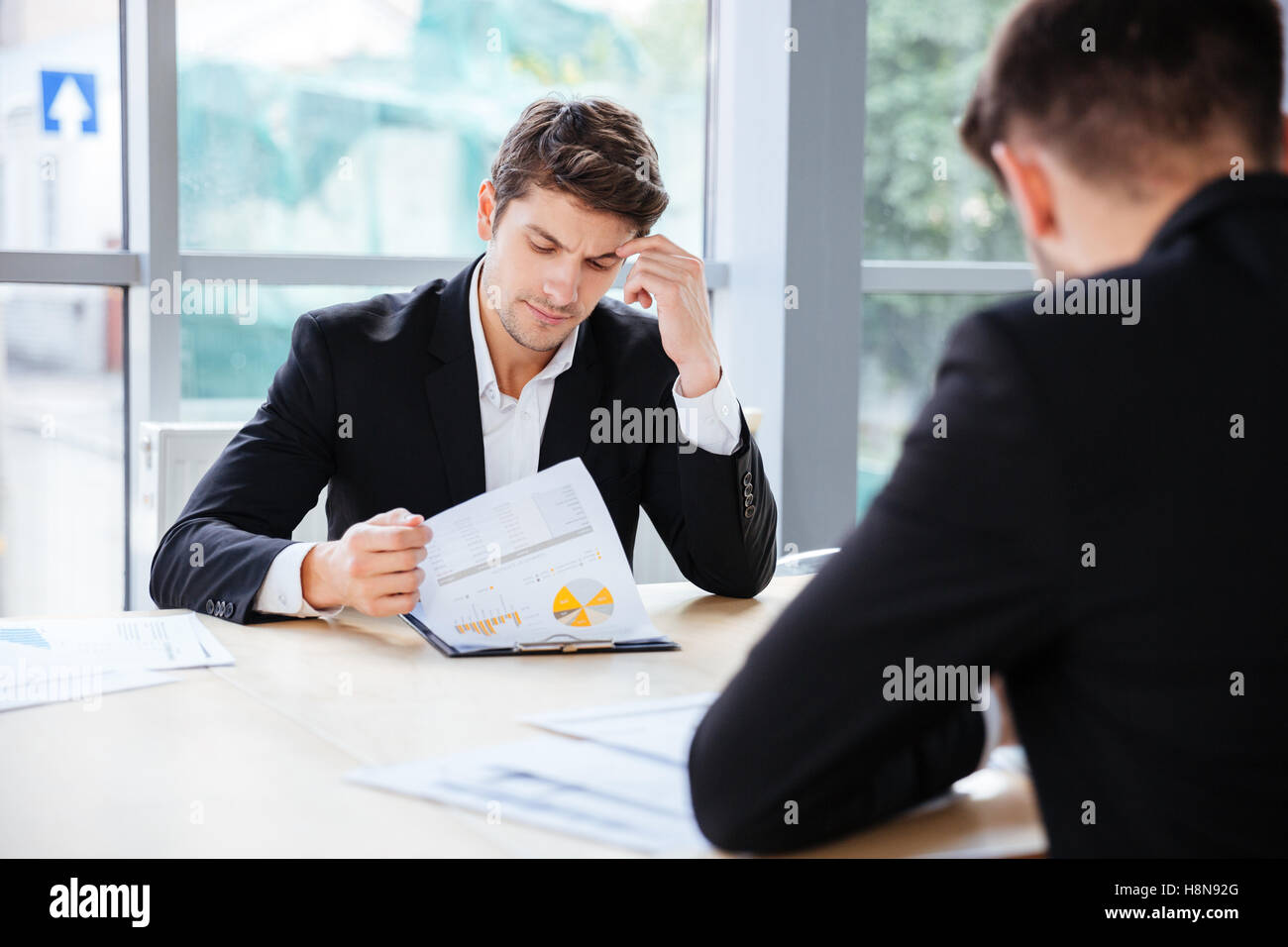 Two thoughtful young businessmen working with business plan in office - Stock Image
