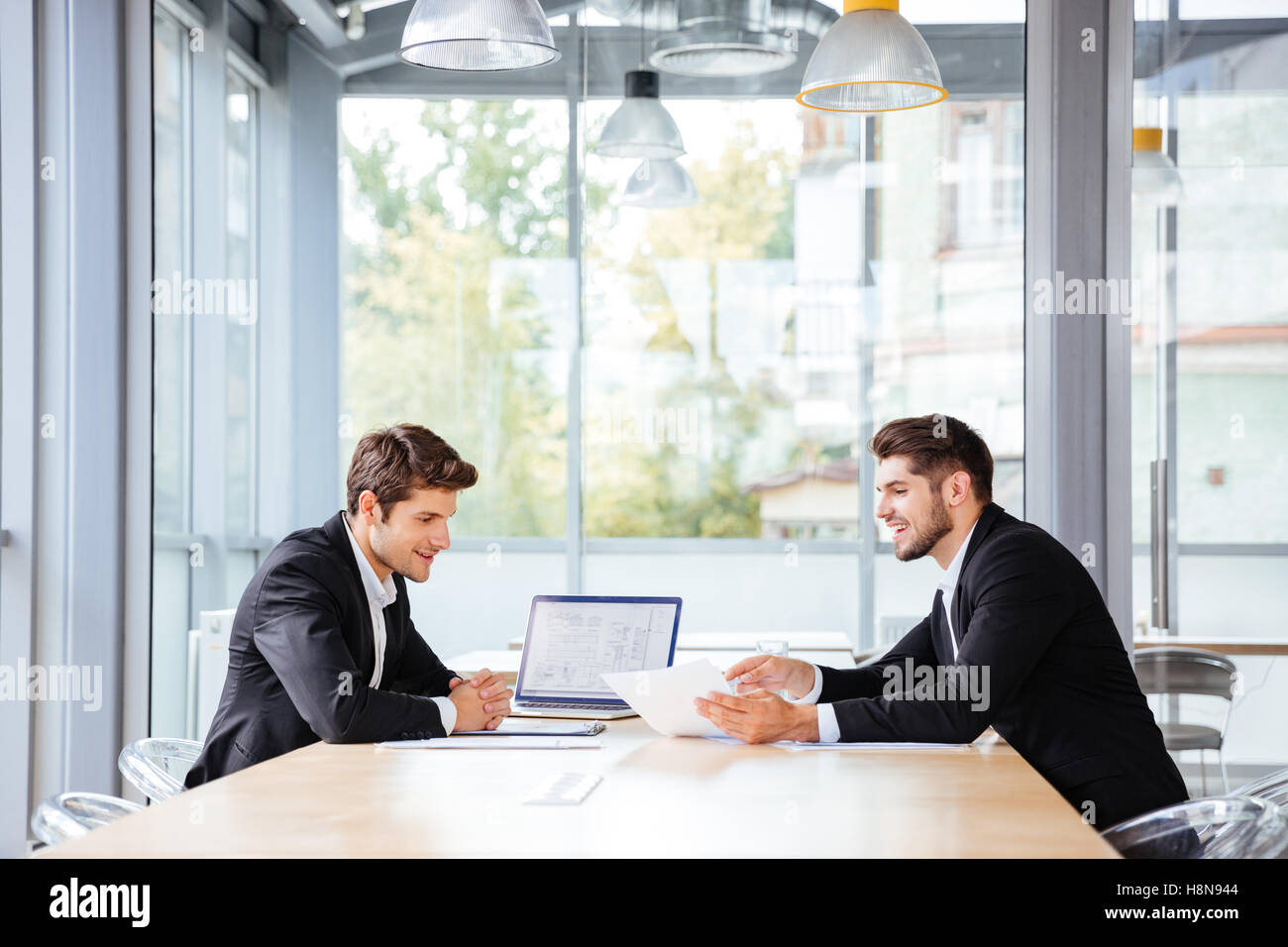 Two happy young businessmen working together using laptop on business meeting in office - Stock Image