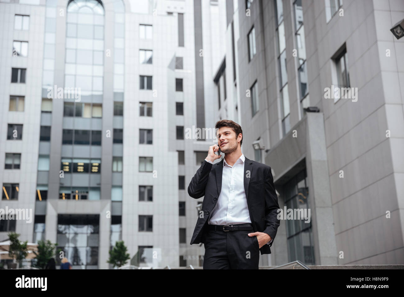 Smiling young businessman talking on mobile phone in the city Stock Photo