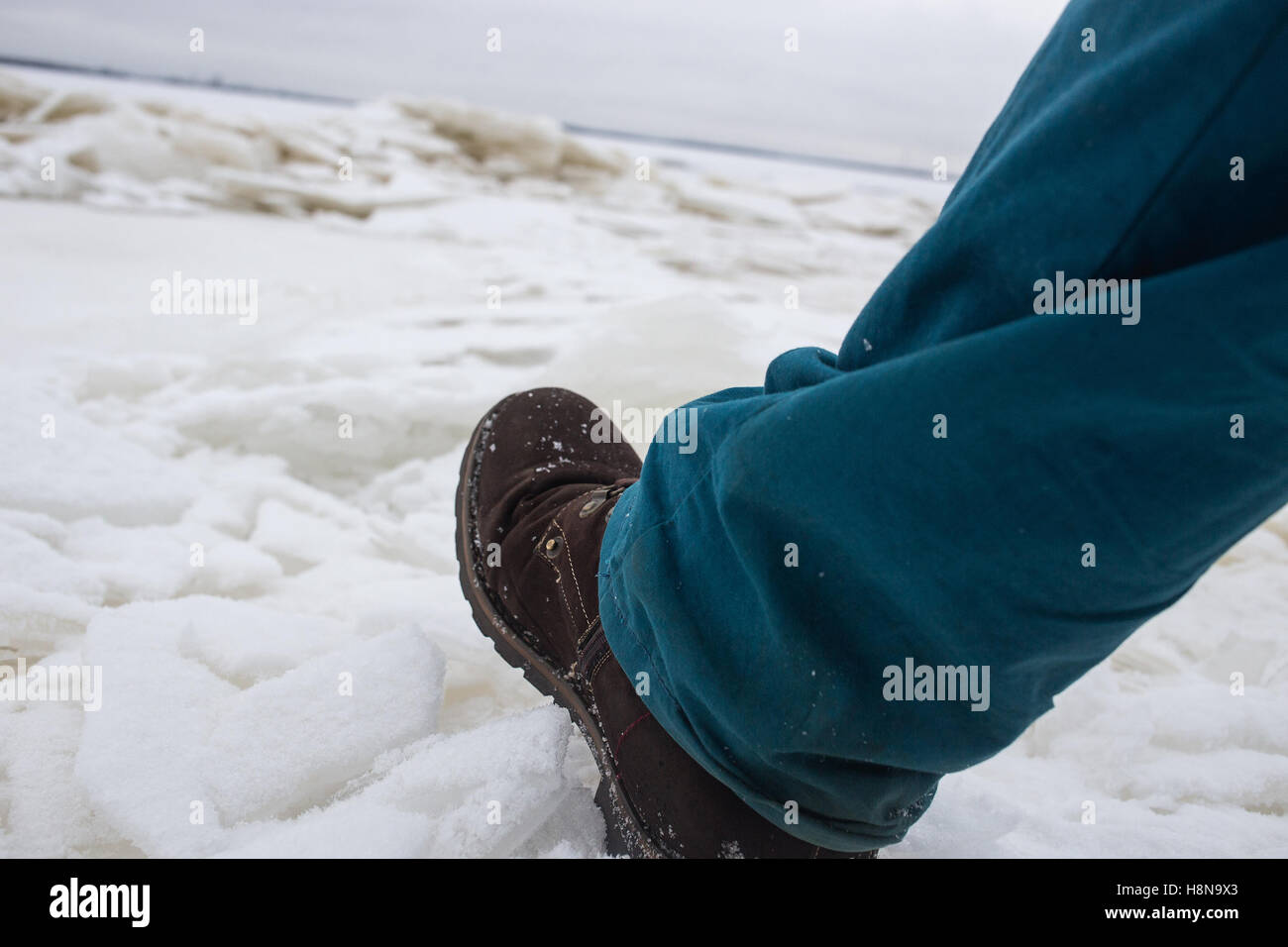Male Feet On The Weak Bad River Ice. Concept Danger Falling Through the ice. - Stock Image