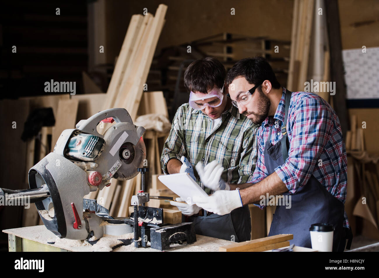 angry boss and worker together in a carpenter's workshop - Stock Image