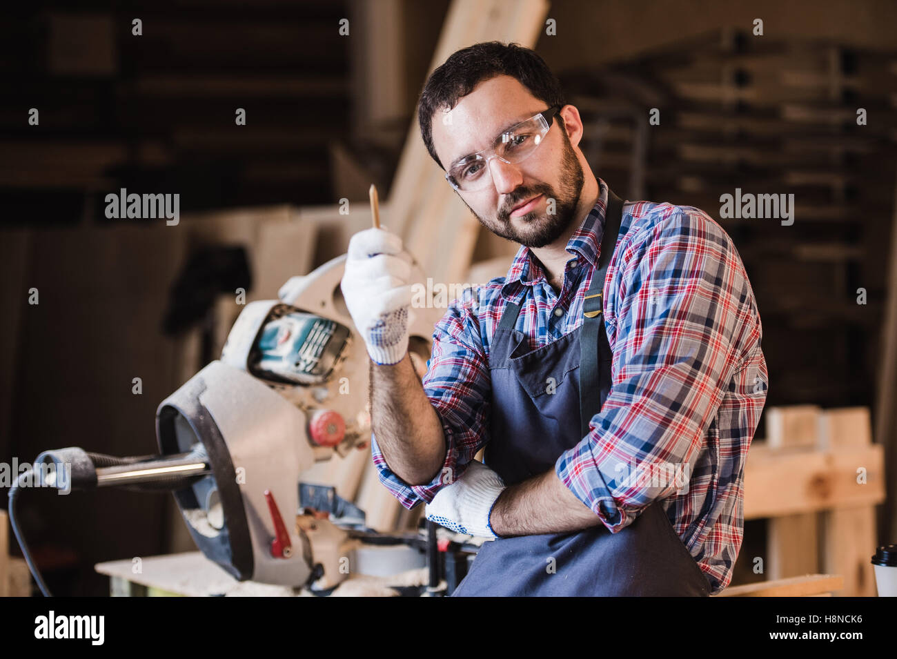 Master sells its own products. Male carpenter have an idea at workshop holding pen in his hand - Stock Image