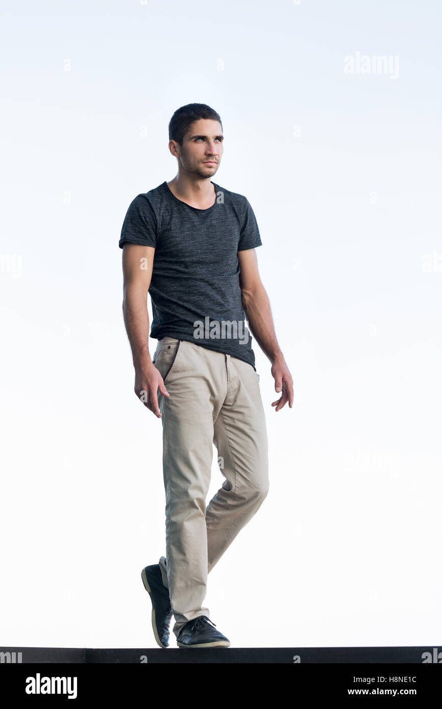 Athletic man in a dark T-shirt on background of sky. Men's beauty. Street fashion. - Stock Image