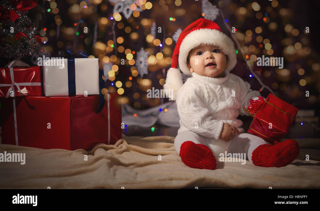 c3845197fb2f3 Little smiling boy (baby) in a white knitted sweater and hat of Santa Claus