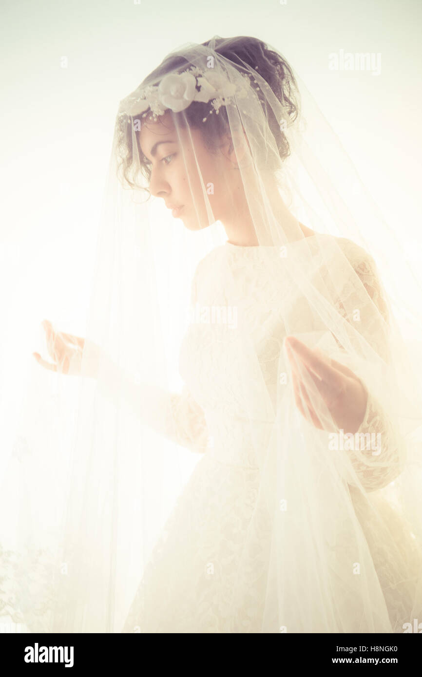 Bridal wedding photography: A young olive skinned woman wearing a white wedding dress and a veil  standing in front Stock Photo
