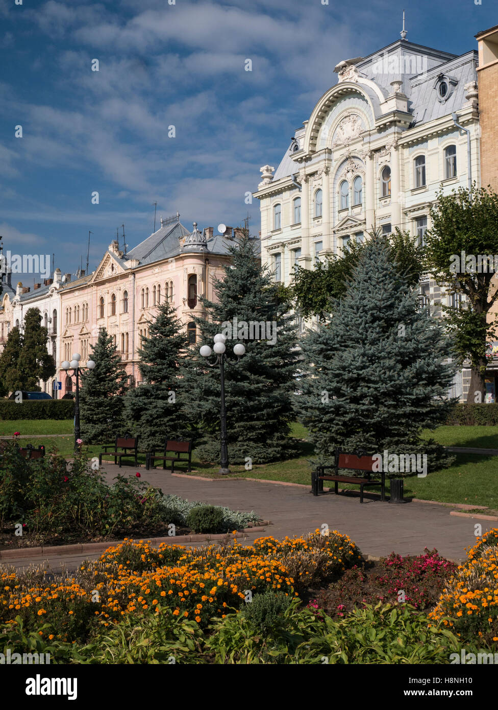 Beautiful buildings surrounding Teatralina Square in Chernivtsi, Ukraine. Pretty flowers are blooming in the foreground - Stock Image