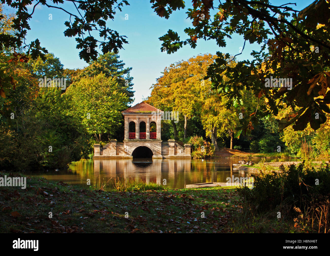 The boathouse at Birkenhead Park, framed by surrounding foliage - Stock Image