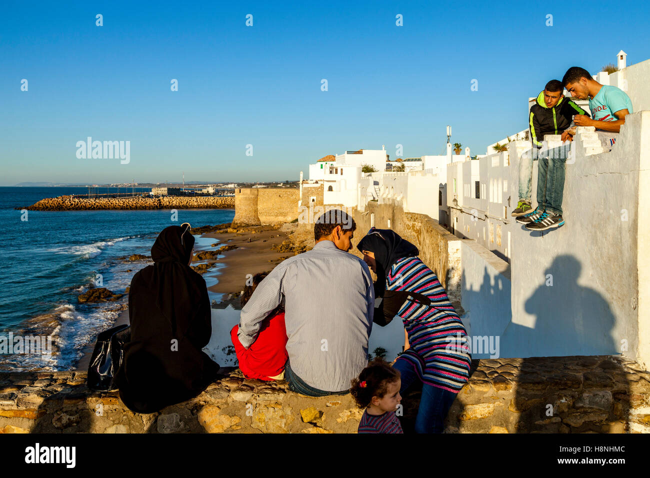 Moroccan People Look Out Over The Walled Medina Of Asilah At Sunset, Asilah, Morocco - Stock Image