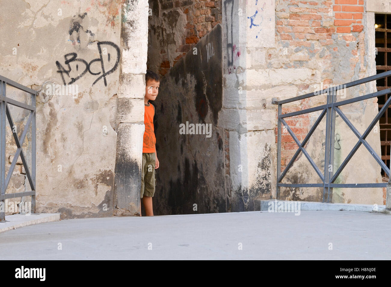 A Boy playing Hide and Seek in the streets of Venice, Italy. Stock Photo
