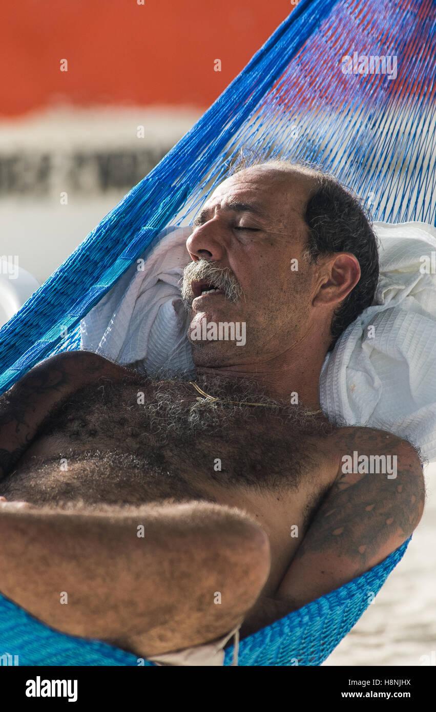 Man sleeping in a hammock on the beach - Stock Image