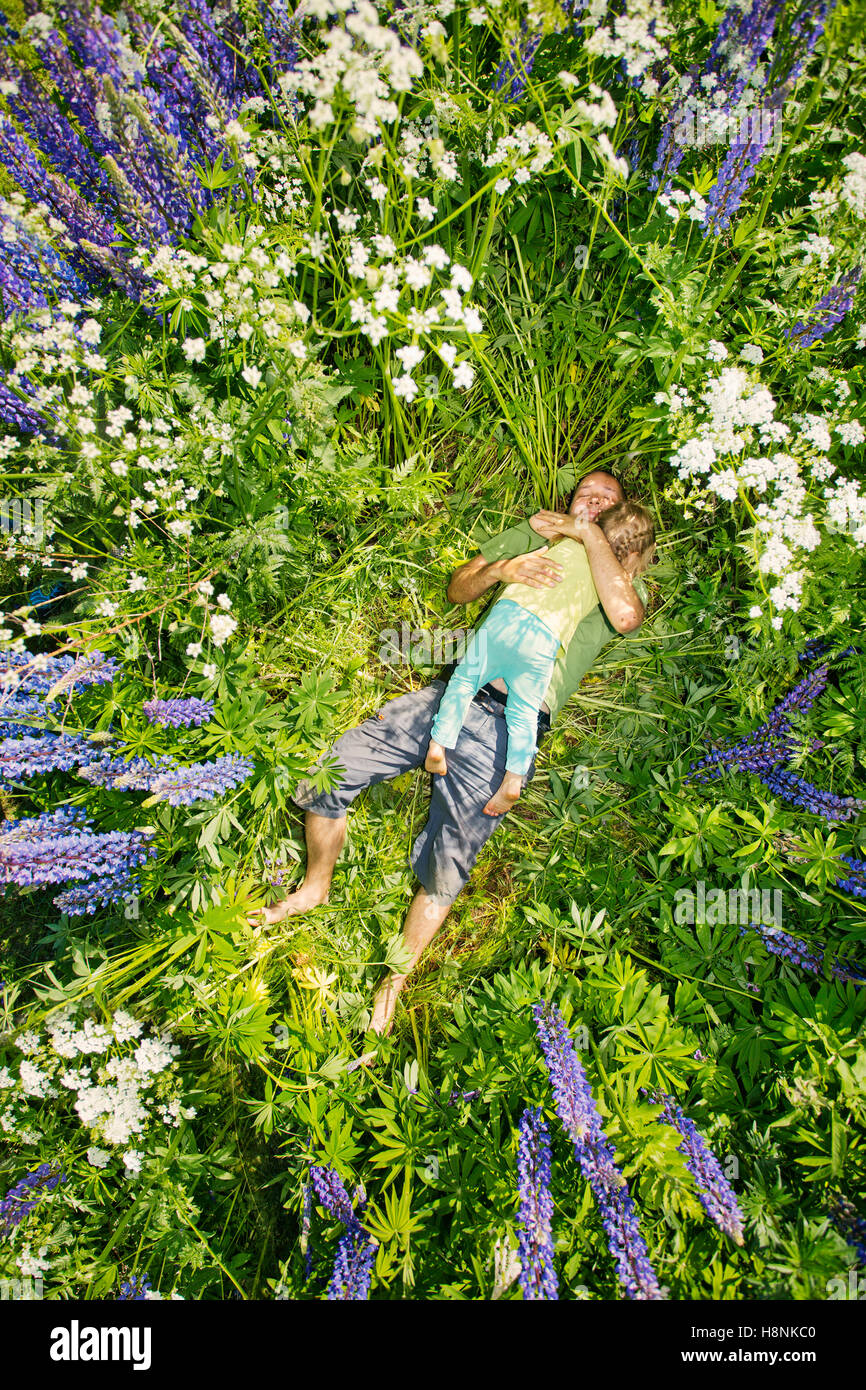 Finland, Man and girl (2-3) lying in meadow Stock Photo