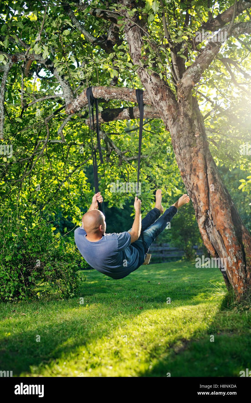 Man swinging on tree swing Stock Photo