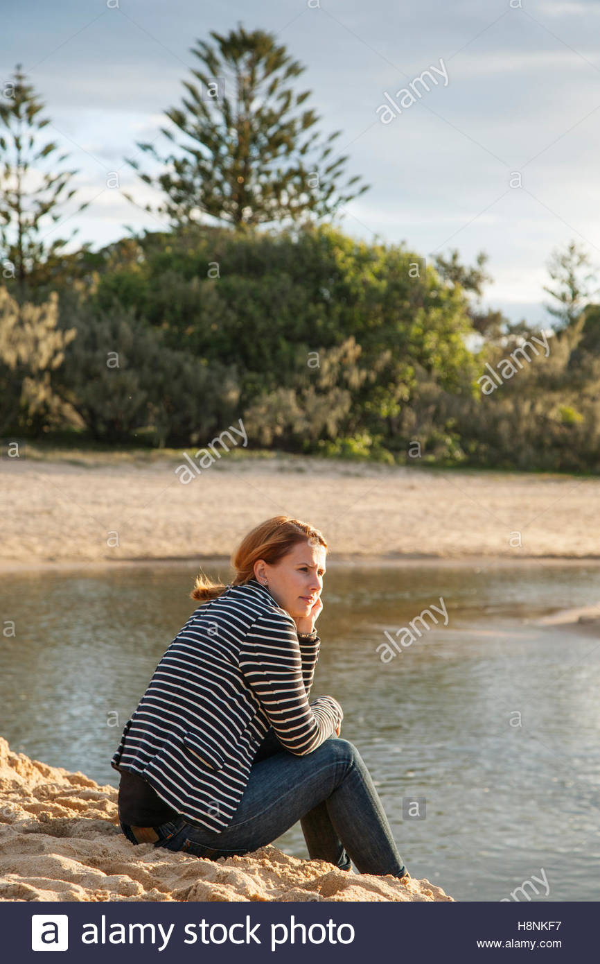 Woman sitting on sand and looking at view - Stock Image