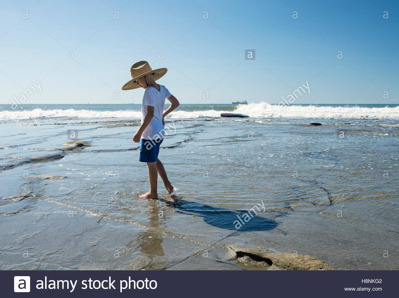 Boy (6-7) in straw hat standing in water on beach - Stock Image
