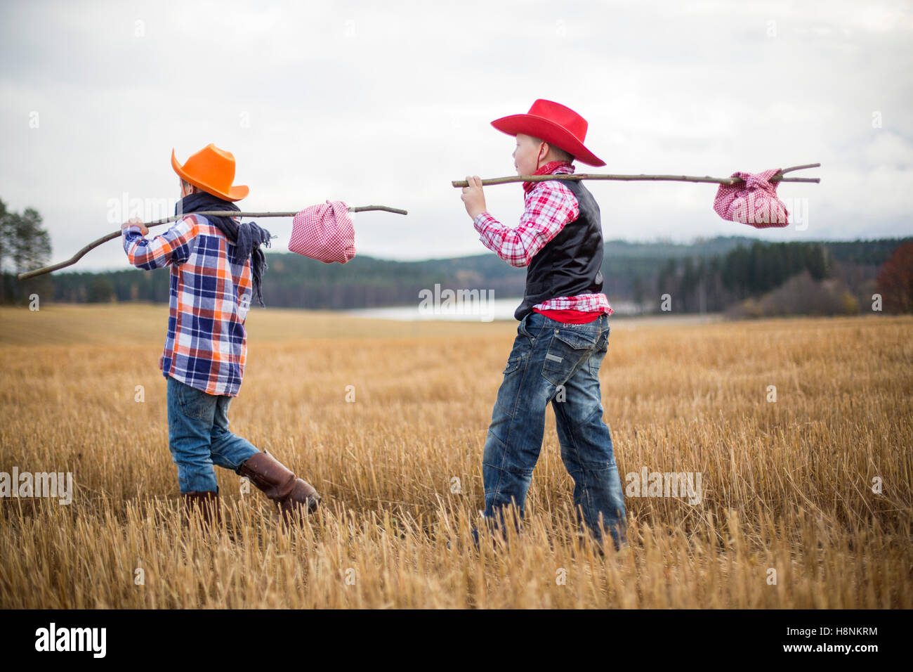 Boys (8-9) wearing cowboy clothes walking in field - Stock Image